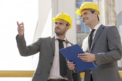 Young male architects with clipboard discussing at construction site Stock Image