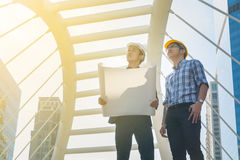 Young Male Architects Discussing with Businessman at Constructio. N Site as Business Industrial Communication Development Concept Stock Photos