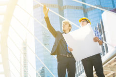 Young Male Architects Discussing with Businessman at Constructio. N Site as Business Industrial Communication Development Concept Royalty Free Stock Images