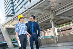 Young Male Architects Discussing with Businessman at Constructio. N Site as Business Industrial Communication Development Concept Royalty Free Stock Photo