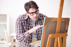 The young male artist drawing pictures in bright studio Royalty Free Stock Image