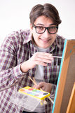 The young male artist drawing pictures in bright studio Royalty Free Stock Photo