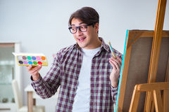 The young male artist drawing pictures in bright studio Royalty Free Stock Photos