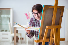 The young male artist drawing pictures in bright studio Stock Photography