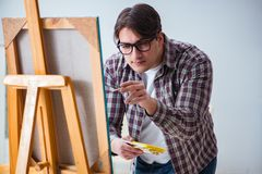 The young male artist drawing pictures in bright studio Royalty Free Stock Images