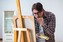 The young male artist drawing pictures in bright studio Stock Images