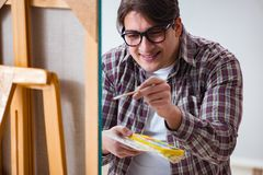 The young male artist drawing pictures in bright studio Stock Photo