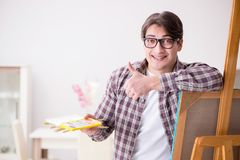 The young male artist drawing pictures in bright studio Stock Image