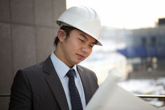 Young male asian architect. Close-up young asian architect with white helmet  looking blueprint serious Royalty Free Stock Photo