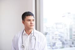 Young male asian doctor looking out of the window at hospital.  Royalty Free Stock Images