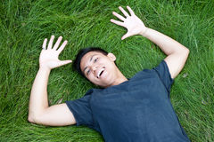 Young male asian student. Lying in the grass Stock Photo
