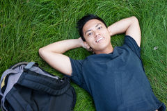 Young male asian student. Lying in the grass with a backpack Stock Photo