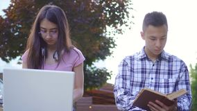 Young male asian student with book and young asian woman with laptop in park stock video footage
