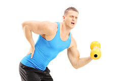 Young male athlete with back pain lifting a dumbbell. Isolated on white background Stock Images