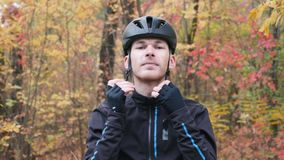 Young male athlete in black cycling clothes standing in fall park and puts on black helmet. Cycling concept. Man cycling.  stock video footage