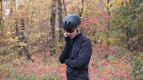 Young male athlete in cycling apparel, helmet and glasses dialing phone number and calling on smartphone before workout in fall fo. Rest. Cycling training in stock video footage
