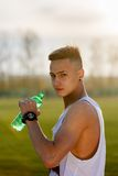 Young male athlete drinking water Stock Image