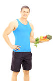Young male athlete holding a dish full of fresh vegetables Royalty Free Stock Images