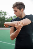 Young male athlete make stretching exercises outdoors. Image of young male athlete make stretching exercises outdoors. Looking aside Royalty Free Stock Images