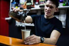 Young male athlete making a protein shake. pours it into a glass stock photography