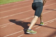 Young male athlete pressing legs on track. Young asian man male athlete warming up stretching legs on track Stock Photos