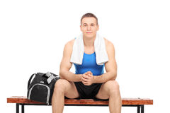 Young male athlete resting seated on a bench Stock Images