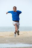 Young male athlete running at the beach. Stock Photo