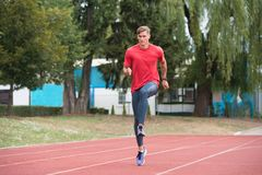 Young Male Athlete Running on Track. Young Athlete Man Running on Track In Park Run Athletics Race Royalty Free Stock Photo