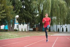 Young Male Athlete Running on Track. Young Athlete Man Running on Track In Park Run Athletics Race Stock Image