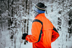 Young male athlete running on winter alley in Park Stock Images