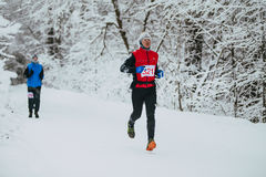 Young male athlete running on winter snowy alley in  Park Royalty Free Stock Image