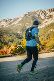 Young male athlete runs in background of mountain landscape Royalty Free Stock Photography