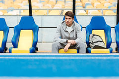 Young male athlete in sportswear sitting on a stadium seats Stock Photography