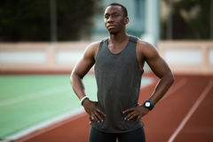 Young male athlete standing at the stadium race track Royalty Free Stock Image