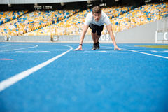 Young male athlete standing in a start position. On a racetrack Stock Photo