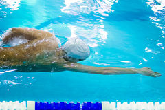 Young male athlete swimming freestyle Royalty Free Stock Image