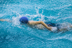 Young male athlete swimming freestyle in pool. around him water splashes Stock Photos