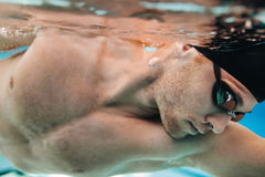 Young male athlete swimming in pool. Close up underwater shot of young male athlete swimming in pool Stock Photo