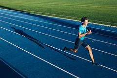 Young male athlete training on a race track. Shot of a young male athlete training on a race track. Sprinter running on athletics tracks royalty free stock images