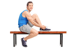 Young male athlete tying his shoelaces. And looking at the camera seated on a wooden bench isolated on white background Stock Photo