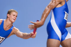 Young male athletes passing relay race baton royalty free stock images