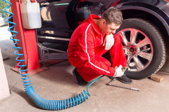 Young male auto mechanic checking the air pressure of a tyre. Crouching down alongside the vehicle with the gauge from the pump in his gloved hand Royalty Free Stock Photo