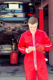 Young male auto mechanic standing making notes Royalty Free Stock Photos