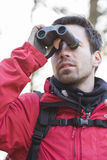 Young male backpacker using binoculars in forest Royalty Free Stock Photos