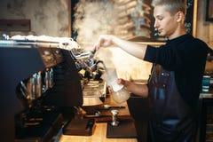 Male barista prepares cappuccino on coffee machine. Young male barista in black apron prepares cappuccino on coffee machine. Professional bartender occupation Stock Photos