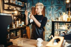Barista checks clean dishes after making coffee. Young male barista checks clean dishes after making coffee at cafe counter. Barman works in cafeteria, bartender Stock Photo