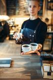 Young male barista holds two cups of fresh coffee. Young male barista in black apron holds in hands two cups of fresh coffee, cafe counter on background Royalty Free Stock Photo