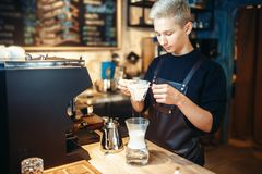 Young male barista makes coffee at the counter. Espresso machine on background. Barman works in cafeteria, bartender occupation Stock Photos