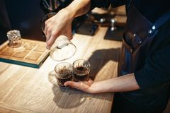 Young male barista makes fresh black coffee. At cafe counter. Barman works in cafeteria, bartender prepares espresso Stock Photography