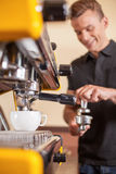 Young male barista making coffee. Royalty Free Stock Photography